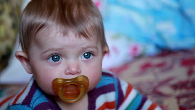 face close-up of a baby with pacifier - pacifier stock videos and b-roll footage