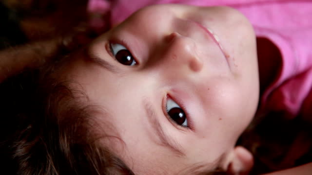 face close-up of a calm little girl looking at camera - lying on back stock videos & royalty-free footage