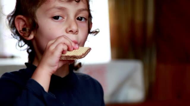 Close-up van het gezicht van een kind kauwen de wafel