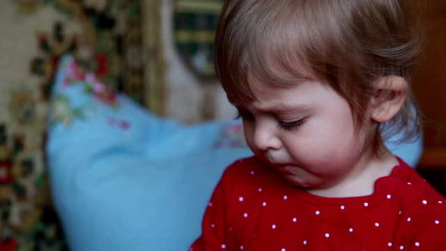 face close-up of a child eating cookie and sweeping crumbs from the bed - housework stock videos & royalty-free footage