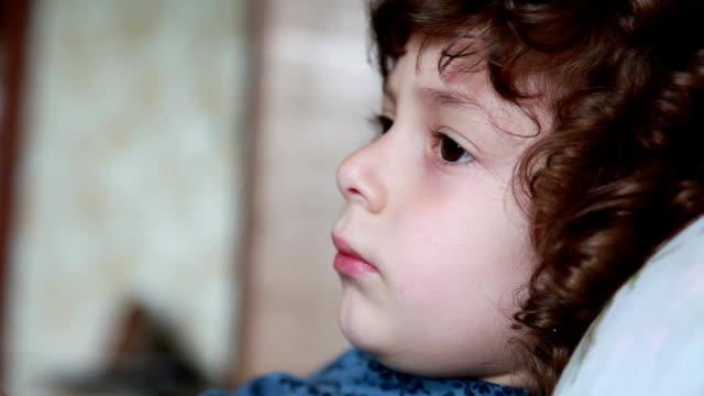 face närbild av en lycklig liten flicka ligger på sängen - profil redigerat segment bildbanksvideor och videomaterial från bakom kulisserna