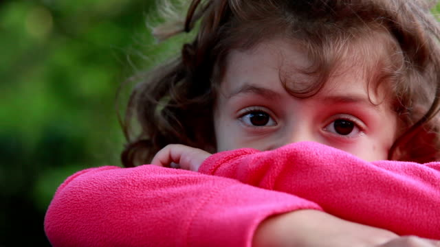 face close-up of a pensive little girl in the backyard - staring stock videos & royalty-free footage