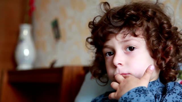 vídeos y material grabado en eventos de stock de primer plano de la cara de una niña pensativa mirando algo - dedo sobre labios