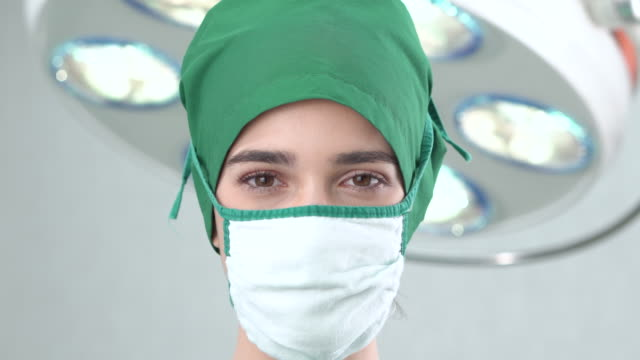 face close-up portrait of female doctor wears a surgical gown in the operating room - operating gown stock videos & royalty-free footage