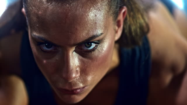 slo mo tu face of a focused female sprinter before start - wettkampf stock-videos und b-roll-filmmaterial