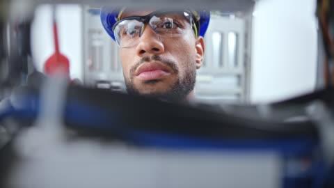 vídeos y material grabado en eventos de stock de ds cara de un electricista macho mirando en el panel eléctrico y conectando cables - examen