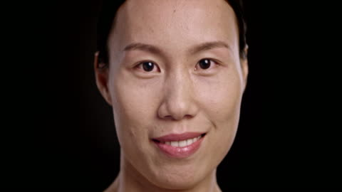 vídeos de stock, filmes e b-roll de rosto de uma mulher asiática sorridente - black background