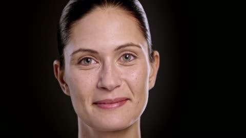 vídeos de stock, filmes e b-roll de rosto de uma jovem mulher sorrindo caucasianas - black background