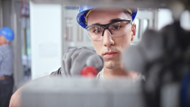 ds gesicht eines jungen männlichen elektrikers, der in die elektrische platte schaut und drähte verbindet - schutzbrille stock-videos und b-roll-filmmaterial