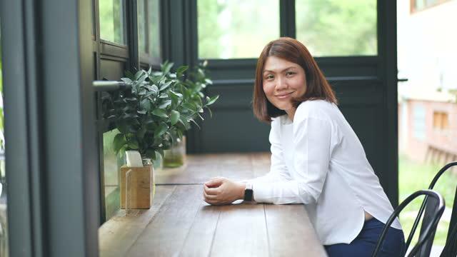 vídeos de stock, filmes e b-roll de rosto de mulher asiática olhando para a câmera e sorrindo - vista frontal