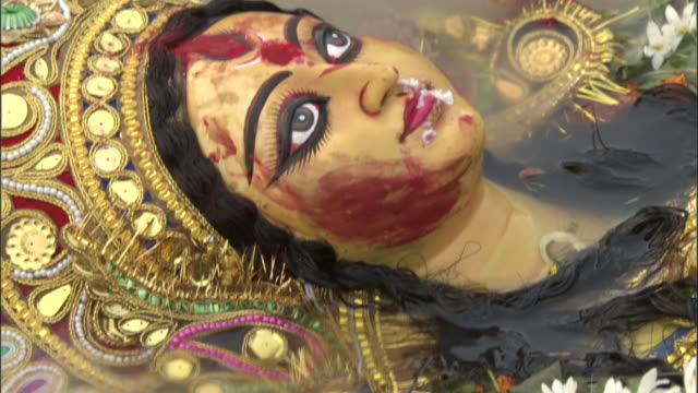 Face of effigy of Hindu goddess floats along in Hooghly river as part of Durga Puja festival, Kolkata Available in HD.
