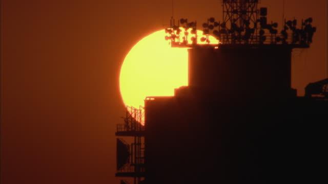 aerial cu face of evening sun behind communications tower, johannesburg, gauteng, south africa - 2007 stock-videos und b-roll-filmmaterial