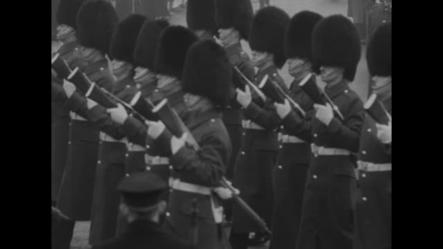 cu face of king's guardsman / guards memorial // at horse guards parade king's guards march in formation carrying rifles reversed / crowd of... - 1952 bildbanksvideor och videomaterial från bakom kulisserna