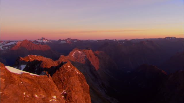 low aerial, face of mt.tutoko in early sun, fiordland national park, new zealand - rock face stock videos and b-roll footage