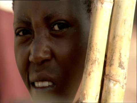 cu face of woman peering out from behind pole / kigali, rwanda - フツ族点の映像素材/bロール
