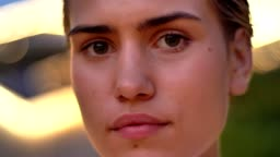 Face of young modern woman is watching at camera in evening, blurred lights on background