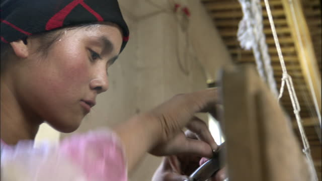 Face of young woman as she prepares shuttle then weaves silk, Hetian, Xinjiang province, China