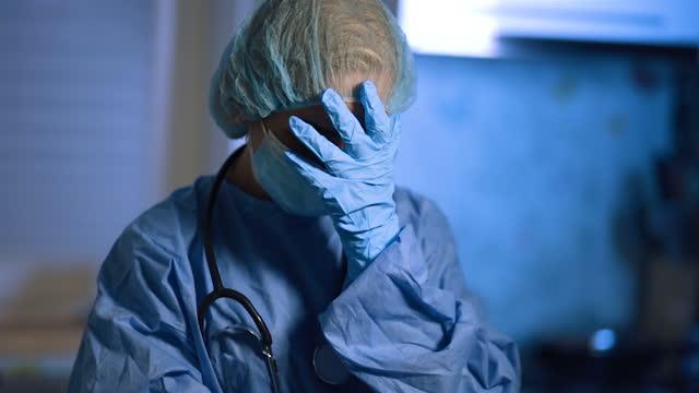 vídeos de stock e filmes b-roll de face palm of female doctor in surgical mask during home visit - bata cirúrgica