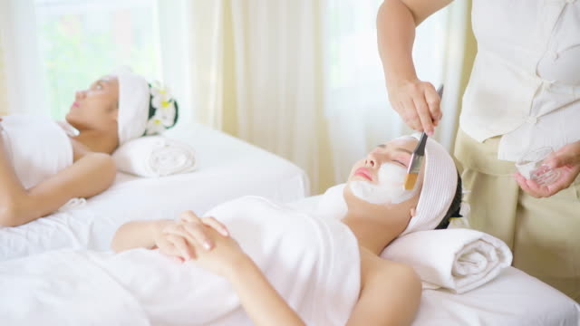 face peeling mask, spa beauty treatment, skincare. woman getting facial care by beautician at spa salon, side view, close-up - spa treatment点の映像素材/bロール