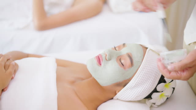 vídeos de stock e filmes b-roll de face peeling mask, spa beauty treatment, skincare. woman getting facial care by beautician at spa salon, side view, close-up - máscara facial