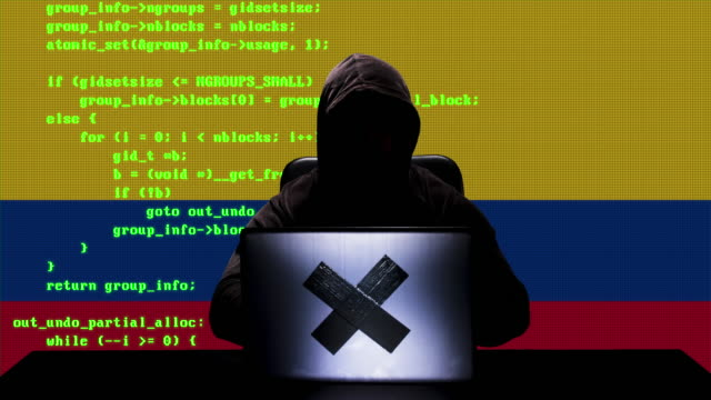 faceless colombian hacker typing code hacking on his laptop with colombia flag in background - colombian flag stock videos and b-roll footage