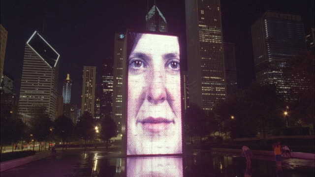 faces appear on a jumbotron in downtown chicago. - large scale screen stock videos & royalty-free footage