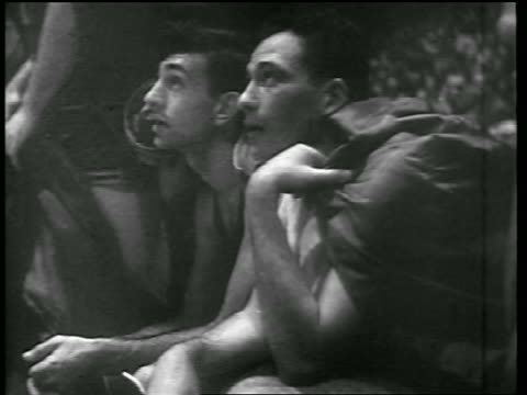 vídeos de stock, filmes e b-roll de b/w 1946 faces of basketball players sitting on bench / huskies vs knicks / news - 1946