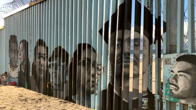 faces of people deported from the united states adorn the usmexico border fence on the beach on september 28 2019 in tijuana mexico the artwork is... - deported stock videos & royalty-free footage