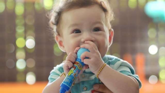 gelaatsuitdrukking door Aziatische jongetje, speelgoed, primaire tanden bijten