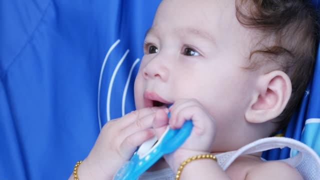 facial expression by asian little boy ,biting toy ,primary teeth - soltanto un neonato maschio video stock e b–roll