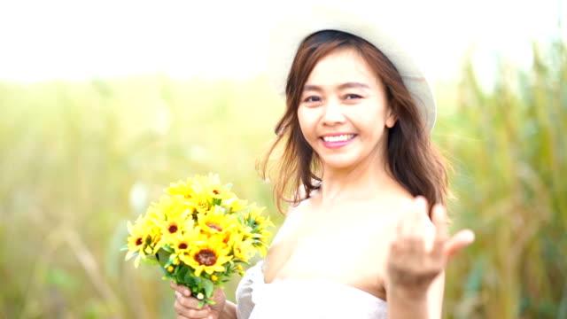 stockvideo's en b-roll-footage met gelaatsuitdrukking door aziatische rijpe vrouw in zonnebloemen veld wenkende en welkom teken - zonnebloem