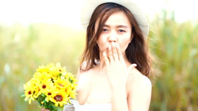 Gesichtsausdruck von Reife Asiatin im Sonnenblumen Feld, weht ein Kuss und Willkommens-Schild
