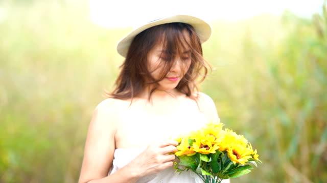 Gesichtsausdruck von Reife Asiatin im Sonnenblumen Feld, Freude, Glück