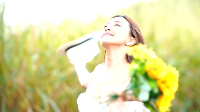 Gesichtsausdruck von Reife Asiatin im Sonnenblumen Feld, das Gefühl von Freiheit mit ausgestreckten Armen