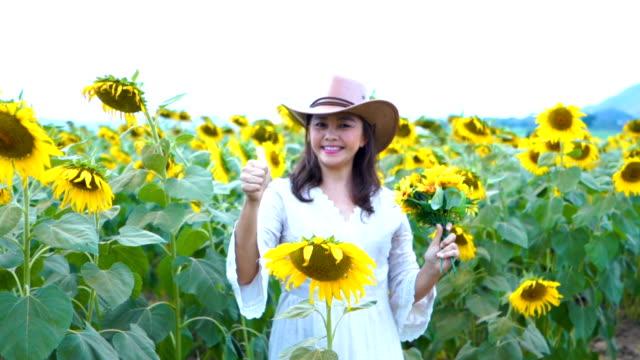 Gesichtsausdruck von Reife Asiatin im Sonnenblumen Feld, gutes Zeichen
