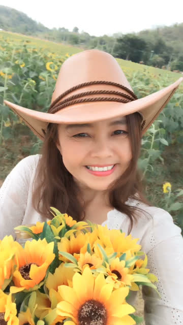 facial expression by Asian mature woman in sunflowers field , vertical video for smart phone