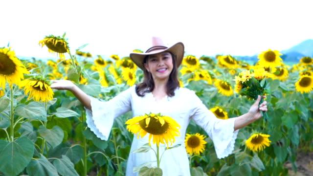 Gesichtsausdruck von Reife Asiatin Willkommensschild Sonnenblumen Feld