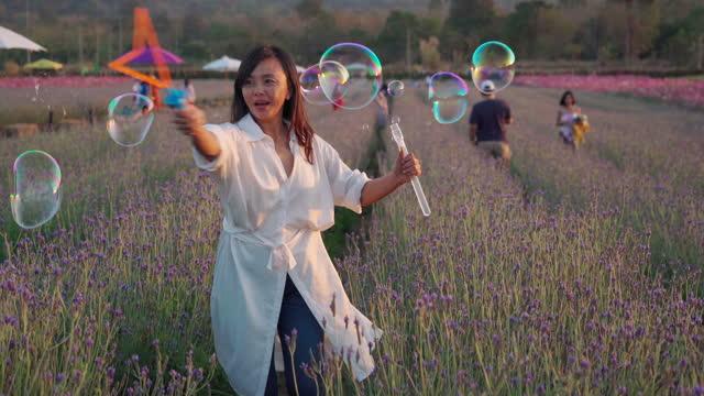 gesichtsausdruck von asiatischen reifen frau ruhen und spielen blase zauberstab in kosmos wiese - menschliche gliedmaßen stock-videos und b-roll-filmmaterial
