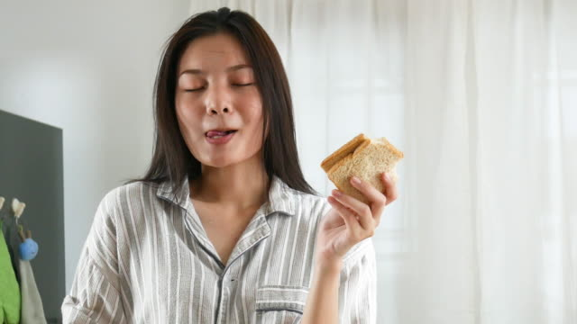 facial expression by young woman in purity morning time , cooking and eating sandwich . licking lips , thumbs up for good condition - good condition stock videos & royalty-free footage