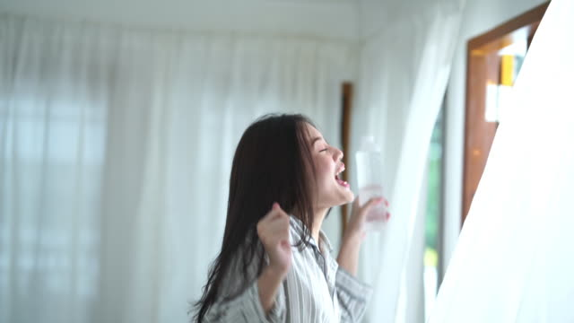 facial expression by young woman in purity morning time  , drink water from bottle - postura video stock e b–roll