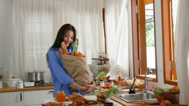 純度の朝の時間に若い女性による表情、朝食を調理するための食材を準備 - 買い物袋点の映像素材/bロール