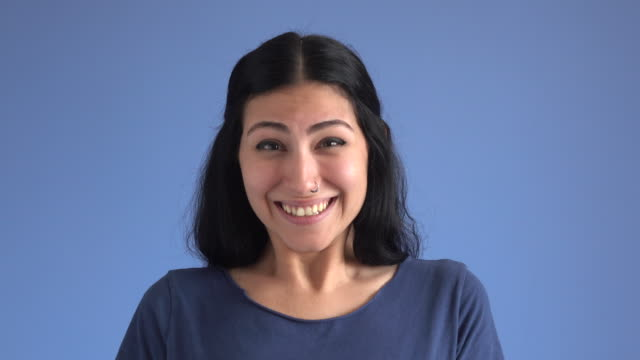 facial expression compilation of adult woman on blue background - colored background stock videos & royalty-free footage
