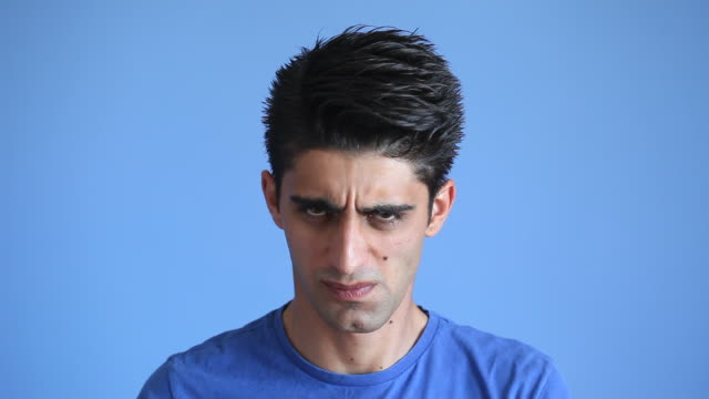 Facial Expression Of Angry Adult Man On Blue Background