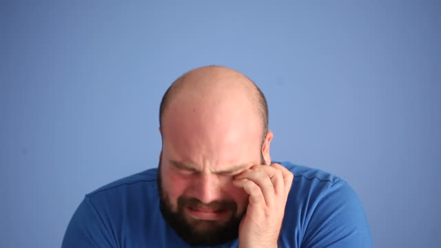 Facial Expression Of Crying Adult Man On Blue Background