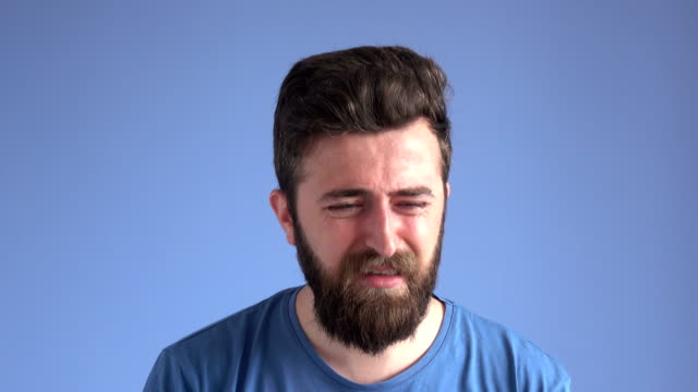 facial expression of crying adult man on blue background - adult stock videos & royalty-free footage