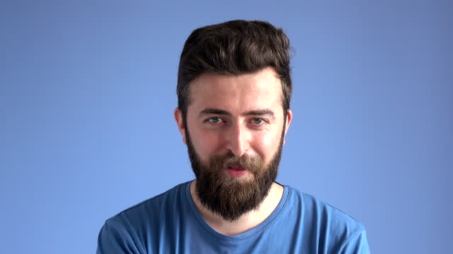 facial expression of flirting adult man on blue background - beard stock videos & royalty-free footage
