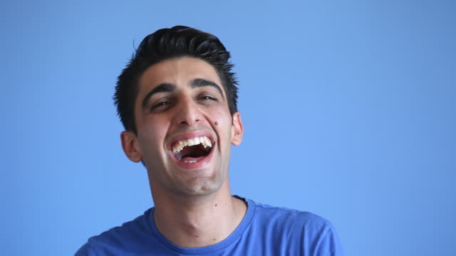 facial expression of laughing adult man on blue background - coloured background stock videos & royalty-free footage