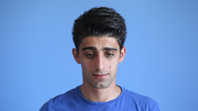 facial expression of shy adult man on blue background - shy stock videos & royalty-free footage