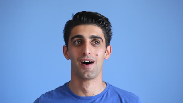 Facial Expression Of Smiling Adult Man On Blue Background