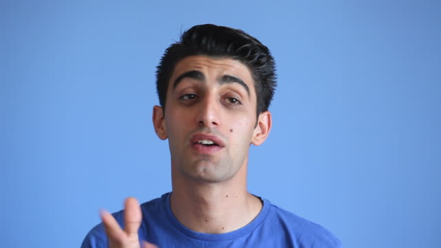 facial expression of talking adult man on blue background - one young man only stock videos & royalty-free footage